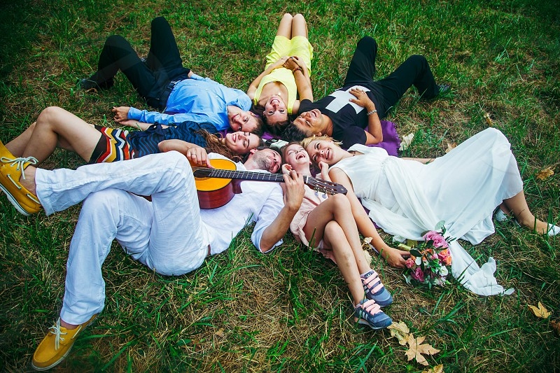 group of people laying on green grass field forming circle during daytime photo