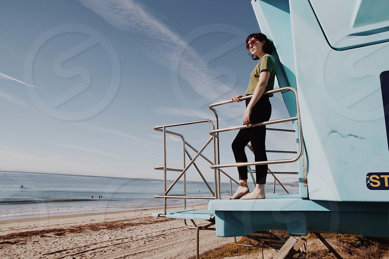 woman standing on life guard station at beach photo