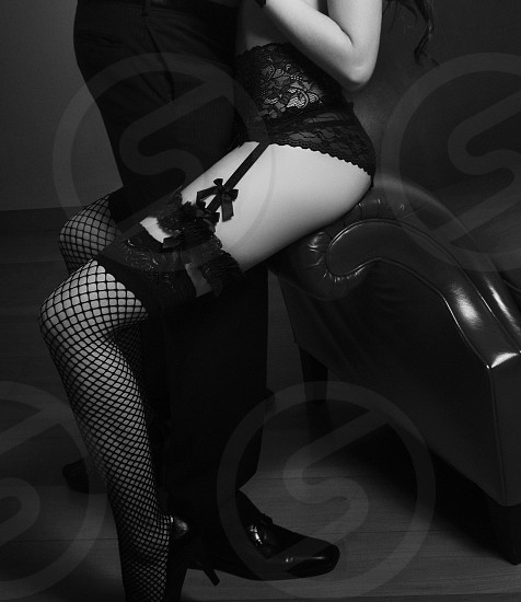 black and white portrait of woman's legs with sexy pose and sexy lingerie and high heels sitting in couch with a fancy dressed man between her legs photo