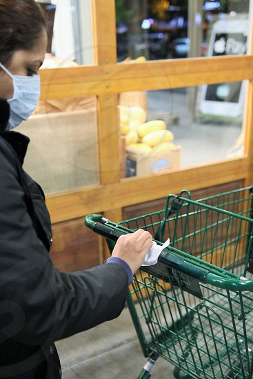 avoiding public germs shopping at grocery store using wipes to clean the cart shopping cart portrait wearing masks cautious  photo
