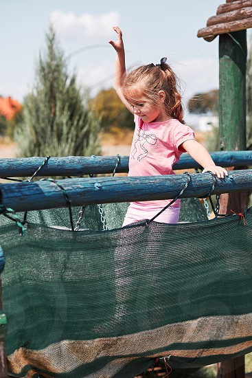 Little adorable girl playing in a home playground in a backyard. Happy smiling kid having fun on a play house on summer day. Real people authentic situations photo