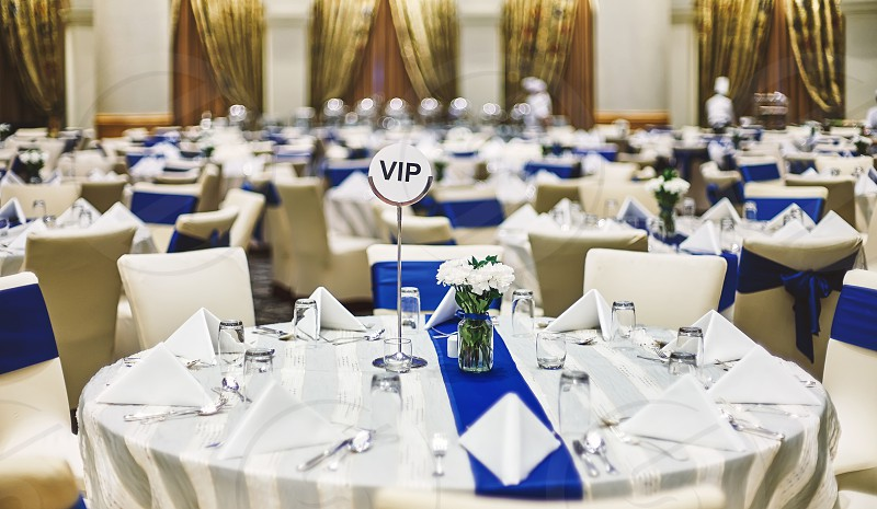 Reception dinner celebration party table setup with dinnerware napkin spoon fork and glasses decoration with blue sash cloth stripe photo