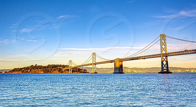 The San Francisco – Oakland Bay Bridge seen from San Francisco Pier 14 with the island of Yerba Buena photo