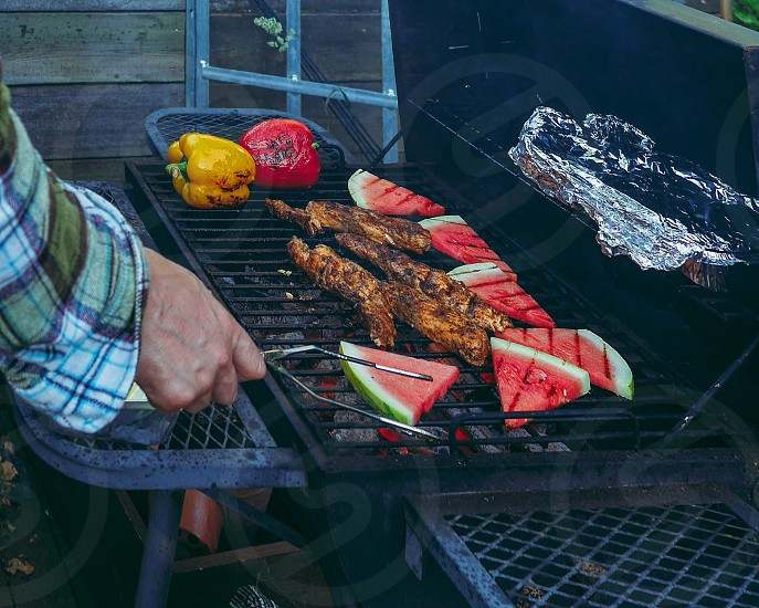 Closeup photo of a man standing grilling watermelon and meat on a grill outdoors photo