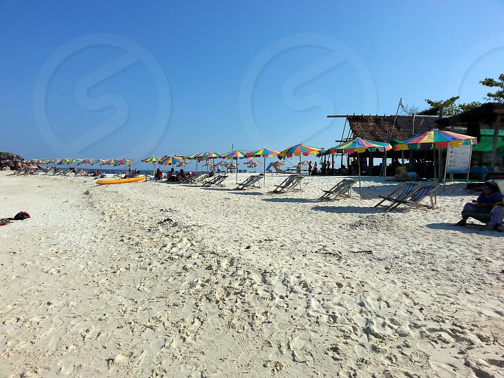 empty beach umbrella and lounge on sea shore under blue sky at daytime photo
