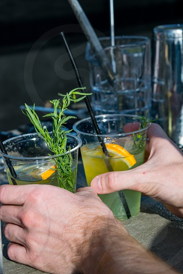 Close up view of male hands holding plastic glasses with fresh cold lemonade and black straws photo
