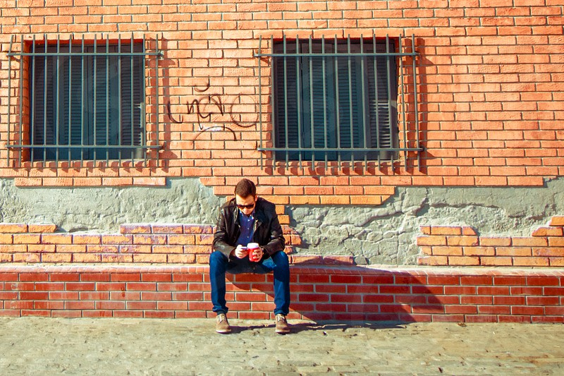 Man Checking His Cellphone And Drinking Coffee photo
