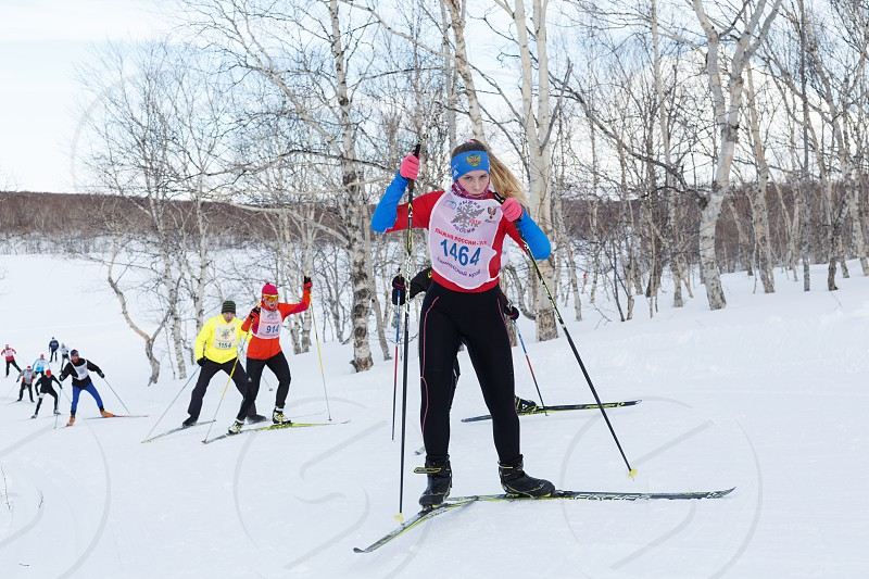 PETROPAVLOVSK KAMCHATKA PENINSULA RUSSIA - FEBRUARY 10 2018: Young sportswoman running on skis in cross-country winter forest. All-Russia mass ski race - Ski Track of Russia. photo