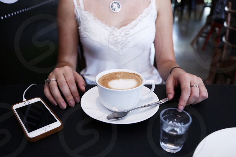 woman with latte water and smart phone photo