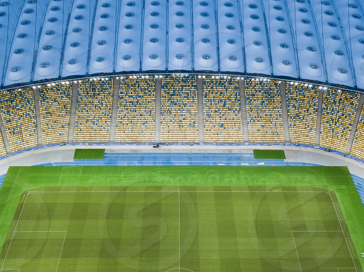 Top view of the blue-yellow stands on a green football field. Aerial view from the drone photo