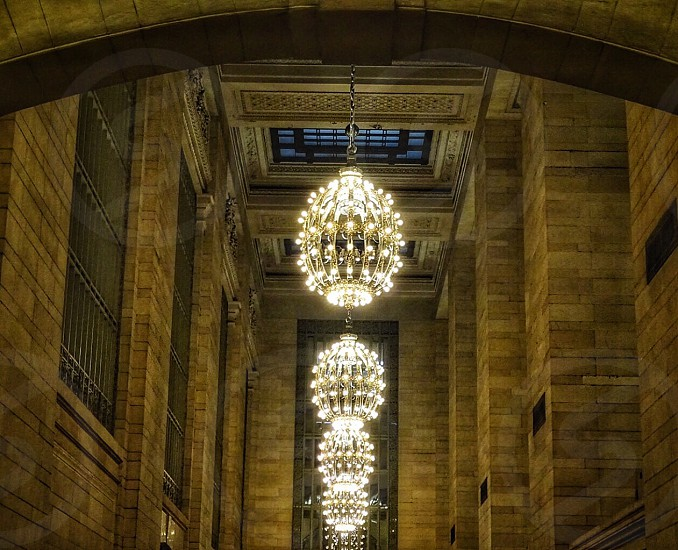 several yellow-lit clear crystal chandeliers on brown bricked high-ceiling rooms photo