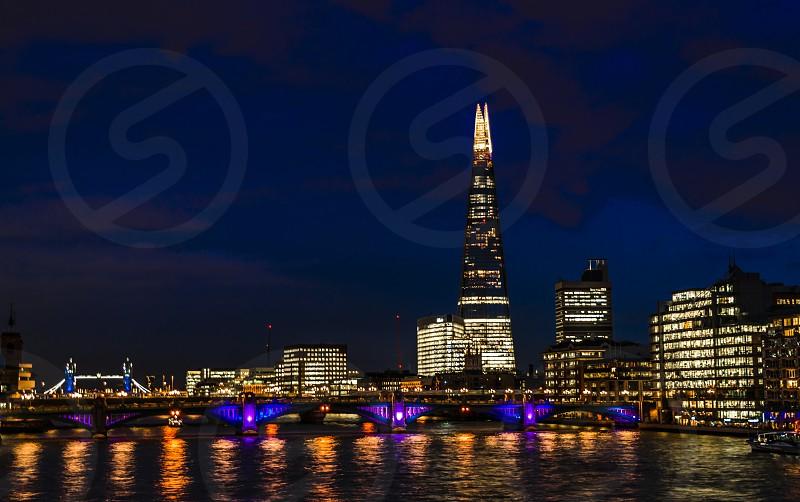 sky grey black white bright lights water shadow city building London high the shard tower bridge royal England river Thames London bridge clouds center night photo