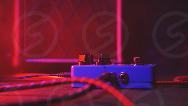 Extremely close up of button for effect electro guitar pedal. Red neon light in night club during show concert photo