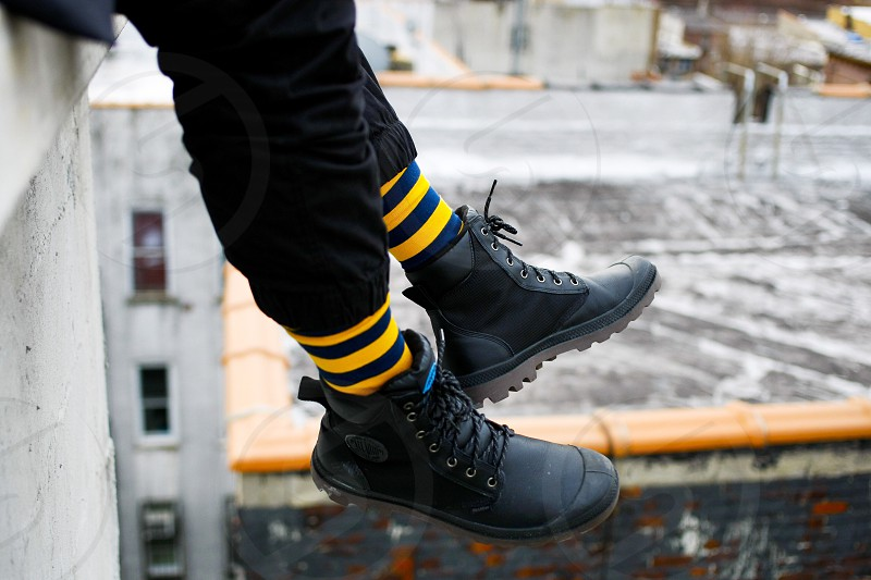 person in black pants black shoes and striped yellow black socks sitting on ledge photo