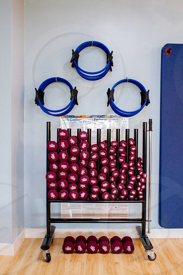 black metal rack with red fixed weight dumbbells and blue hoops hanged on top photo