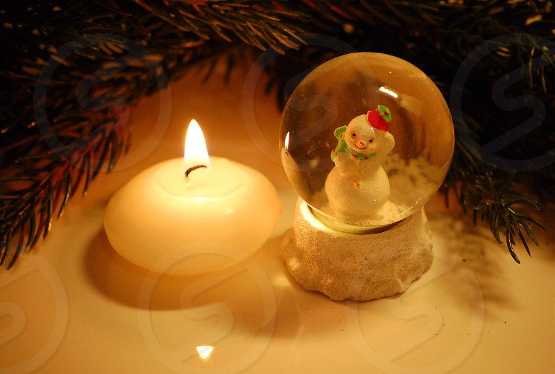 snow globe with snowman inside  and white candle photo