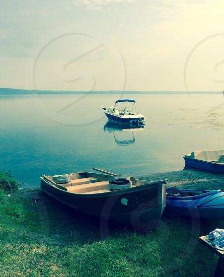 white motorboat on bodies of water near shoreline photo