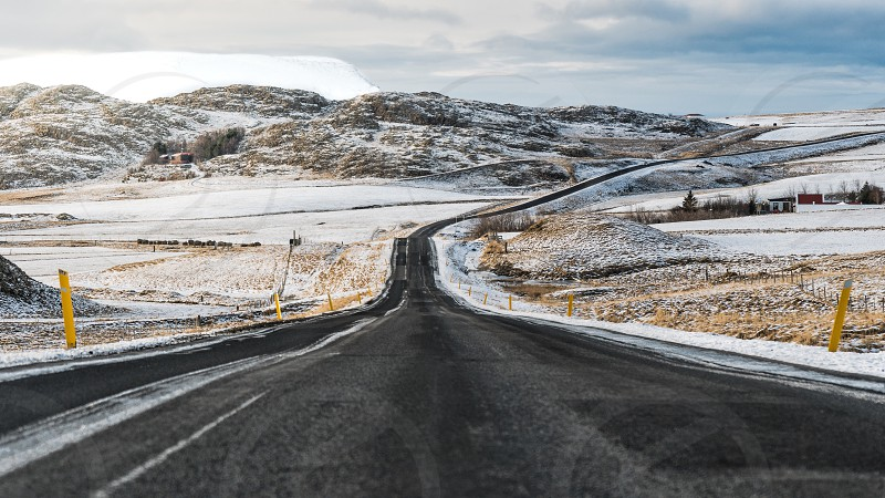 Road tripping in Iceland surrounded my mountains and farm land photo