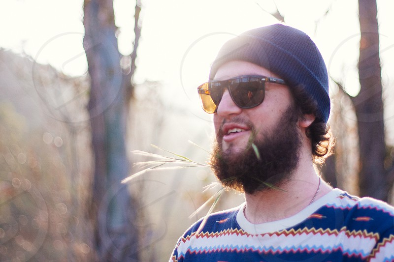man with beard in knit cap and sunglasses in forest photo