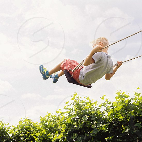 Boy high in the air on a swing photo