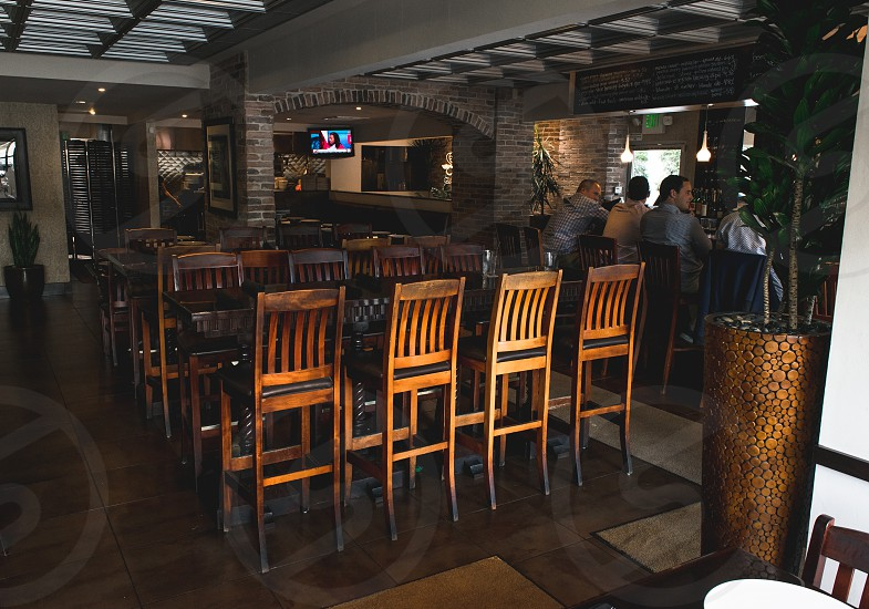 restaurant with chairs and tables near bar with 4 people sitting on bar stools during daytime photo