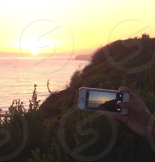 person capturing the sunset in white Apple iPhone 5 photo