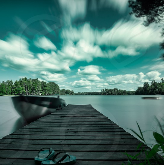 black flip flops on brown wooden dock photo