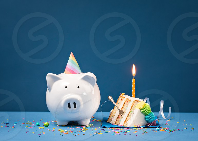 Slice of Cake with one Candle and Piggy Bank over a blue background. Birthday Money Concept. photo