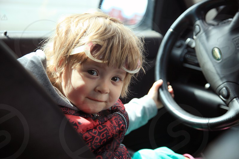 girl sitting in front of black steering wheel photo