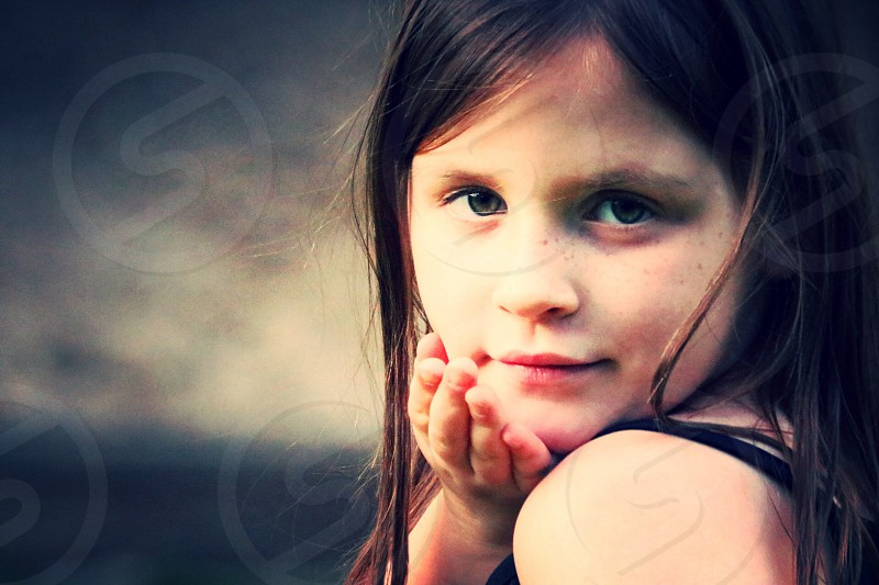 selective focus photography of girl in black top with her right hand on her chin photo