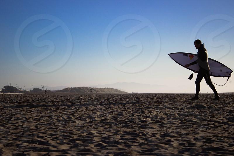 Surfer carrying his surfboard in Ocean Beach. SF - wetsuit surf sand beach ocean.  photo