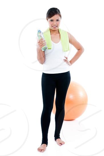 Full-length portrait of fitness woman holding water bottle on white background photo
