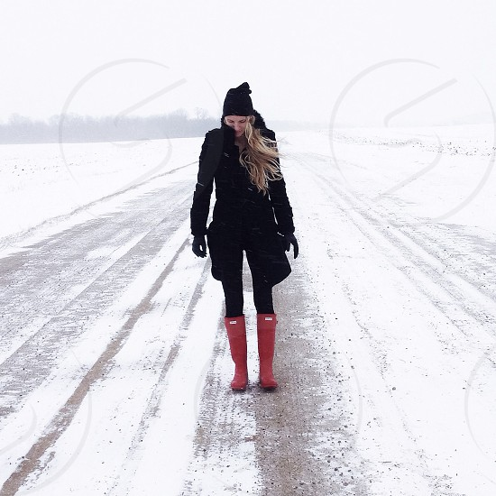 woman in black winter coat and pants with pink galoshes photo