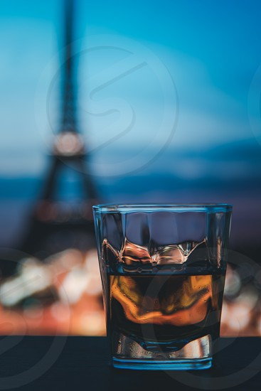Whiskey in a glass beside bottle with Eiffel tower in the background at night. photo