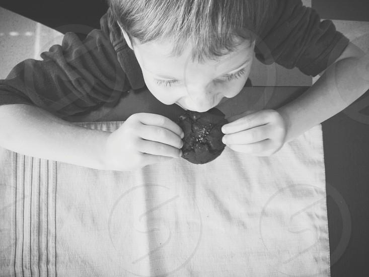 boy wearing black sweatshirt eating cookie photo
