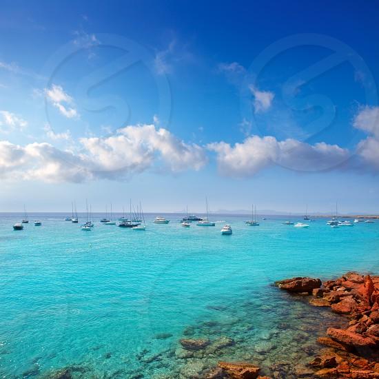 Cala saona in summer with many boats anchored in aqua Mediterranean photo