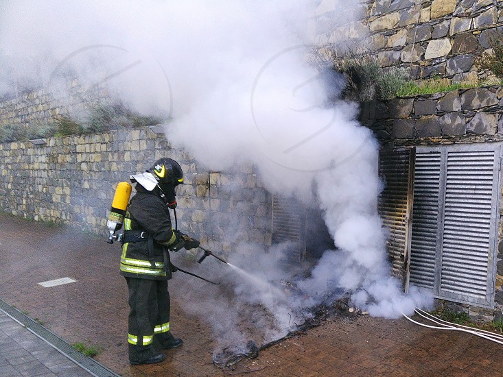 Fireman at work to extinguish a fire photo