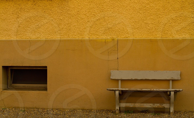brown wooden bench near the wall photo