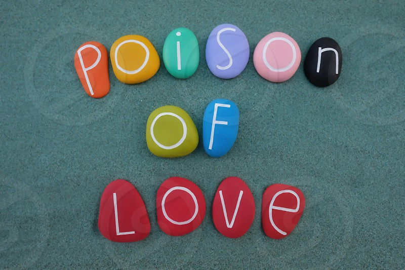 Poison of love creative text composed with multi colored stones over green sand photo