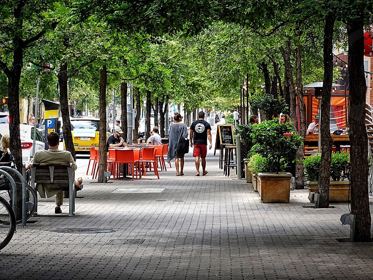 man and woman walking on alley along side road with people sitting on table setups photo