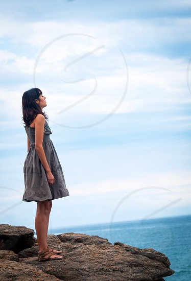 woman wearing a grey dress standing on a rock photo