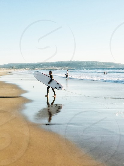 man in black wet suit holding white surfboard by the seashore during daytime photo