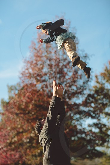 Boy being thrown into the air by his father. photo