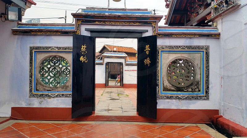 photo of white concrete wall with black wooden kanji script printed pull and push door gate photo