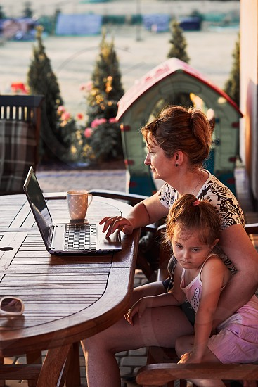 Mother working at home using portable computer sitting on patio with her daughter on summer day photo