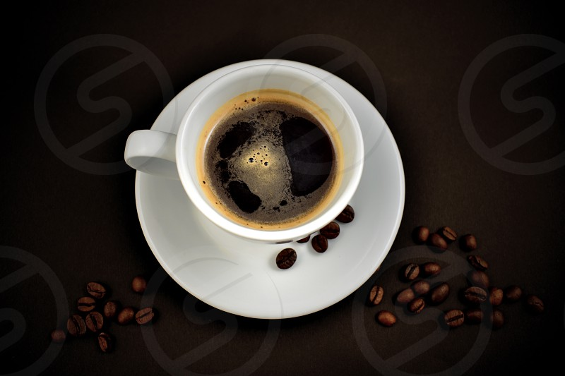 White cup of coffee. White cup of coffee on a black background. Cup of coffee with coffee beans photo