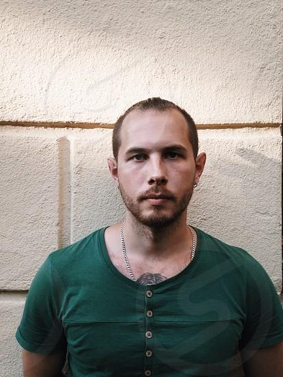 man in green button shirt standing beside wall photo