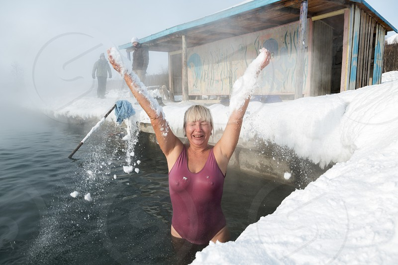 KAMCHATKA PENINSULA RUSSIA - FEB 02 2013: Woman have a thermal bath in hot spring pool in the winter. Eurasia Russian Far East Kamchatsky Krai Anavgay Village. photo