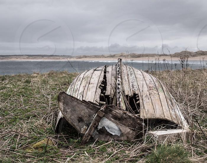 Old boat weathered abandoned boat on shore. photo