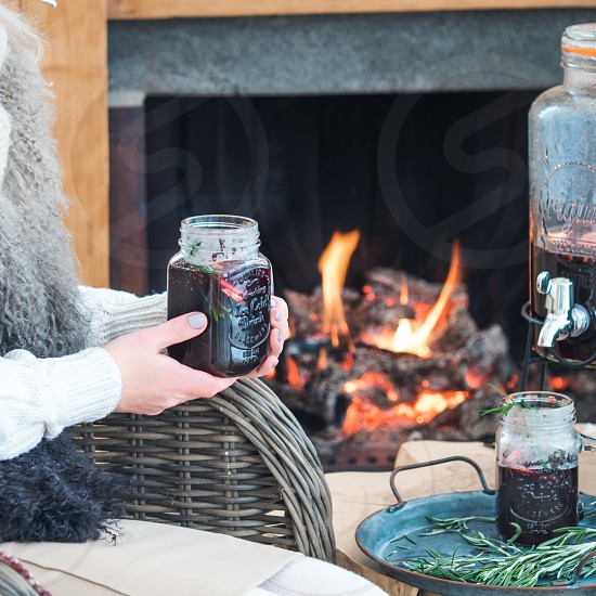 Mulled wine in female hands near fireplace. Winter holiday mood background. Square format. Copy space for text. photo